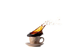 Cup of Spilling black Coffee Creating a Splash royalty free stock photo