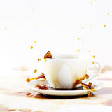 Cup of spilling coffee creating beautiful splash Royalty Free Stock Photography
