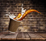 Cup with splashing coffee and milk liquid on wooden table. Take away hot drink Royalty Free Stock Images