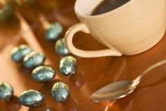 Cup, spoon and egg. Cup of coffee, spon, and eggs of chocolate with golden reflection Royalty Free Stock Photo