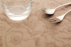 Cup and spoon and fork. On the table Royalty Free Stock Image