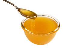 Cup and spoonful of honey. Isolated on white, clipping path included Royalty Free Stock Photography