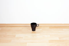 Cup standing on the floor Royalty Free Stock Image
