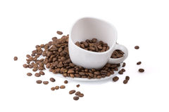 Cup standing on a plate with full of roasted coffee beans. Royalty Free Stock Photo