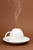 Cup with steam. Coffee cup with steam on brown background Royalty Free Stock Photography