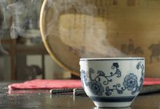 Cup with steam. Hot ready hot prapared tea seeping and steaming in a antique flowered oriental white china cup on black table with stream of steam in front of a Stock Photo