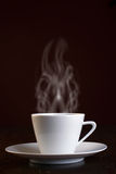 Cup of steaming hot coffee. Over dark background stock photography