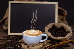 Cup of coffee and coffee beans. Cup of steaming hot coffee and canvas sack of coffee beans, blackboard  as background  suitable for  inclusion of limited  menu Stock Photos