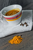 Cup of steaming hot soup with spices on raw cotton embroidered t Stock Photography