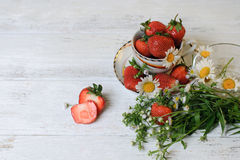 Cup with strawberries and wild flowers Royalty Free Stock Photos