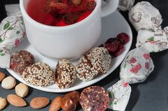 Cup of strawberry tea with handmade candies stock photography
