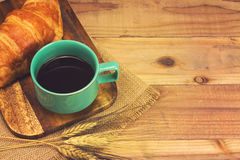 A cup of strong black espresso coffee and fresh croissant Royalty Free Stock Photography