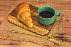 A cup of strong black espresso coffee and fresh croissant Royalty Free Stock Images