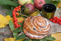 A cup of strong black tea, sweet bun with raisins, ash berries, apples and colorful autumn leaves on a stone surface Royalty Free Stock Images