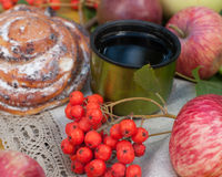 A cup of strong black tea, sweet bun with raisins, ash berries, apples and colorful autumn leaves on a stone surface Stock Photos