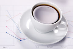 Cup of strong coffee over business diagrams Stock Images