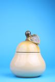 Cup sugar-bowl in the form of a pear. Isolated on blue background Royalty Free Stock Photography