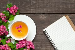 Cup of summer flower tea with pink blossoming branches and blank lined notebook. Over rustic wooden background. top view with copy space Royalty Free Stock Image