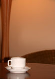 Cup on a table. A porcelain white cup on a wooden table Stock Image