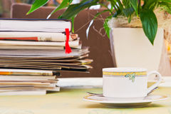 Cup on a table with papers and newspapers Stock Image