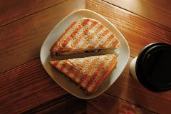 Cup of take away coffee and sandwich on plate Royalty Free Stock Photography