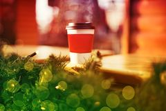 Cup takeaway coffee on cafe veranda with bokeh lights.  stock image