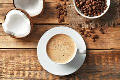 Cup of tasty coconut coffee and beans. On wooden table royalty free stock photos