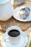 Cup of tasty coffee with a sweet croissant. Cup of tasty, black coffee with a sweet croissant Royalty Free Stock Images