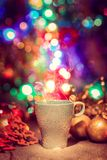 Cup of tasty hot cocoa, on wooden table, with shiny background Royalty Free Stock Photography
