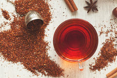 Cup of tasty organic herbal rooibos red tea with. Glass cup of tasty organic herbal rooibos red tea with spices on vintage table background. Top view Royalty Free Stock Photos