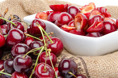 Cup of tasty pitted cherries and whole cherries Stock Photos