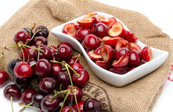 Cup of tasty pitted cherries and whole cherries Royalty Free Stock Photo