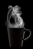 Cup of tea. Silhouette of a steaming cup of something in black background Stock Photography