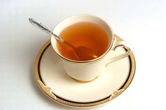 Cup of Tea. A cup full of tea with a spoon inside on a saucer Royalty Free Stock Photography