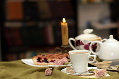 Cup of tea. Against a background of burning candles, cake, flowers and old photographs Stock Images