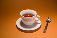 Cup of tea. White cup of tea on plate with spoon beside Stock Image
