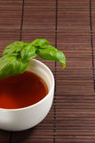 A cup of tea. Calming tea in a tea cup on a bamboo mat with basil leaves Stock Photos