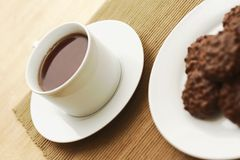 Cup of tea. Black strong tea in white cup and source on the table set on place mat with chocolate biscuits on white plate in the foreground Stock Photo