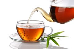 Cup of tea. Tea being poured into glass tea cup, isolated on a white background Royalty Free Stock Photo