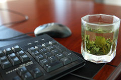 A cup of tea. Beside the keyboard on the desk Stock Images