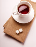 A cup of tea. White cup of tea on a napkin with pieces of sugar royalty free stock photos