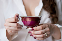 Cup of tea. Hands holding the cup of tea Stock Photography
