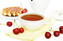 Cup of tea. On yellow napkin with cherries Royalty Free Stock Photo