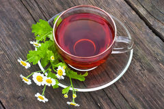 Cup of tea. Tea in glass cup and chamomile on wooden table Royalty Free Stock Images