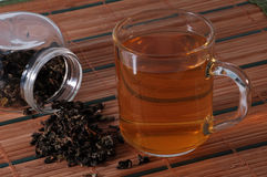 Cup of tea. And tea leaves on bamboo background stock photos