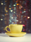 A cup of tea. Yellow cup of tea in the background bokeh in the form of hearts. Illustration on the Valentine's Day Royalty Free Stock Photos