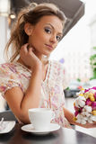 Cup of tea. A beautiful young woman are sitting in a cafe and drinking tea. Outdoors Stock Images