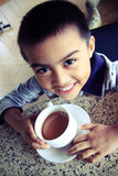 A Cup of Tea. An Asian boy is having a cup of tea Royalty Free Stock Image