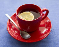 Cup of tea. Hot tea with lemon in red cup royalty free stock photo