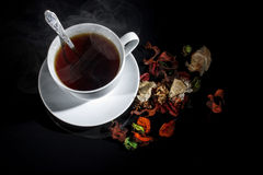 Cup of tea. On a black background, colorful elements complement the overall picture Stock Image